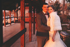 Groom and bride near arbour at sunset Stock Photos