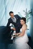 Groom and the bride near a grand piano Royalty Free Stock Photos