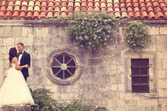 Groom and bride near an old building Royalty Free Stock Image