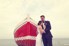 Groom and bride near a red boat Stock Image