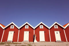 Groom and bride near red houses Stock Photo