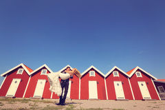 Groom and bride near red houses Royalty Free Stock Photos