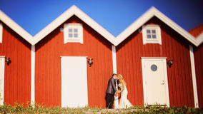 Groom and bride near red houses Royalty Free Stock Image