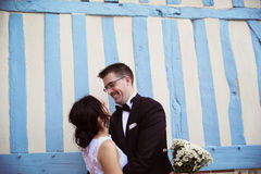 Groom and bride near a stripped wall Stock Image
