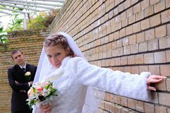 The groom and the bride near a wall Stock Photography