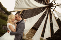 Groom and bride near a windmill Stock Images