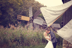 Groom and bride near a windmill Royalty Free Stock Photo