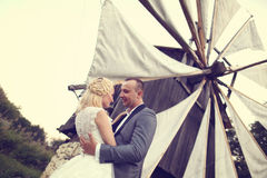 Groom and bride near a windmill Royalty Free Stock Photography