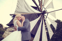 Groom and bride near a windmill Stock Photography