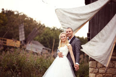 Groom and bride near a windmill Royalty Free Stock Image