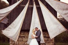 Groom and bride near a windmill Stock Photos