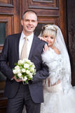 Groom and bride near a wooden door Royalty Free Stock Photos