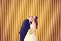 Groom and bride near a yello wall Stock Photos
