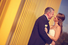 Groom and bride near a yellow wall Royalty Free Stock Images