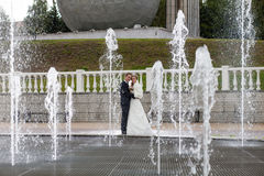 Groom and bride next to a fountain and water jets Stock Images