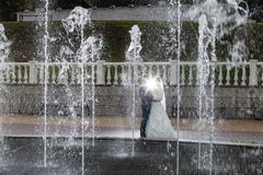 Groom and bride next to a fountain and water jets Royalty Free Stock Photos