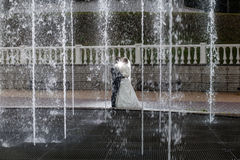 Groom and bride next to a fountain and water jets Royalty Free Stock Images