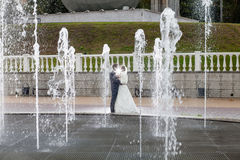 Groom and bride next to a fountain and water jets Royalty Free Stock Image