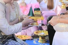 Groom and bride offering tray of gift to older  in traditional Thai wedding ceremony. Concept of marriage. Stock Photo