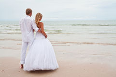 Groom and bride ona beach. Groom and bride barefoot on a beach looking to horizon Royalty Free Stock Photo