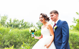 Groom and Bride in a park. wedding dress. Bridal wedding bouquet of flowers Royalty Free Stock Photos