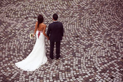 Groom and bride on pavement. Bride and groom on pavement stock photos