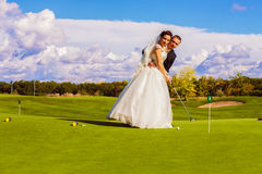Groom and bride playing golf Royalty Free Stock Photography
