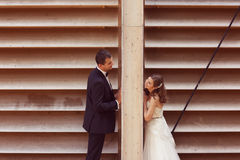 Groom and bride posing near a stripped wooden wall Royalty Free Stock Photography