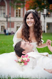 Groom and bride relaxing on a grass Royalty Free Stock Images