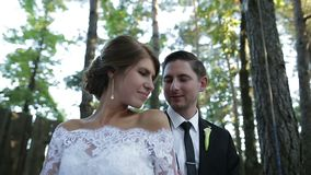 Groom and bride roll on rope. Pretty young couple bride and groom in a wedding dress on a swing outdoor. Groom caress his bride stock footage