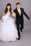 Groom and bride run in studio Royalty Free Stock Photo