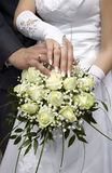 Groom and bride showing gold rings and flowers Stock Image