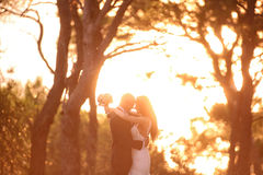 Groom and bride silhouettes in the sunlight Stock Photos