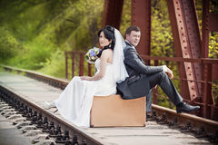 Groom and  bride sit on a suitcase on railway rails Stock Image