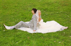 Groom and bride sitting back to back Stock Photos