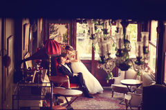 Groom and bride sitting in a beautiful decorated room Royalty Free Stock Photo