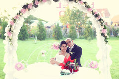 Groom and bride sitting on a bench in the garden Stock Image