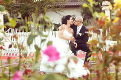 Groom and bride sitting on a bench in the garden Stock Images