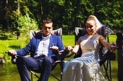 Groom and bride sitting in chairs Royalty Free Stock Images