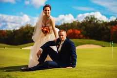 Groom and bride sitting on golf field Stock Images