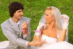Groom and bride sitting on green grass royalty free stock photos