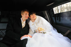 Groom and bride sitting inside limousine Stock Images
