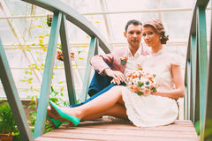 Groom and bride sitting on small bridge Royalty Free Stock Images
