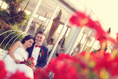Groom and bride sorrounded by red flowers Royalty Free Stock Photo