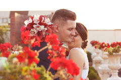 Groom and bride sorrounded by red flowers Royalty Free Stock Images