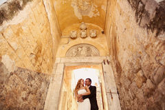 Groom and bride on stairs in a hallway Royalty Free Stock Image