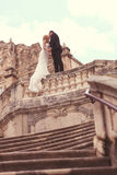 Groom and bride on stairs of a old building Stock Photos