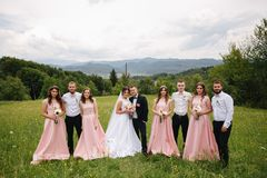 Groom and bride stand with groomsman and bridesmaid. Newlyweds kissing with friends. Wedding day. Background of. Groom and bride stand with groomsman and royalty free stock photos