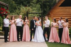 Groom and bride stand with groomsman and bridesmaid outside. Newlyweds kissing and friend clap. Wedding day.  royalty free stock image