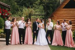 Groom and bride stand with groomsman and bridesmaid outside. Newlyweds kissing and friend clap. Wedding day.  stock photos